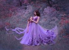 Aantrekkelijke jonge moeder met donker golvend haar en haar weinig dochter, die zich in het bos in lang verbazen verenigen royalty-vrije stock afbeelding