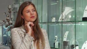 Aantrekkelijke jonge onderneemster die voor juwelen bij de opslag winkelen stock video