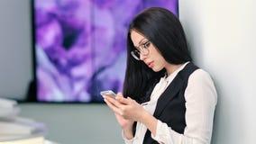 Aantrekkelijke jonge onderneemster in glazen die smartphone gebruiken bij futuristische hi-tech tentoonstelling stock video