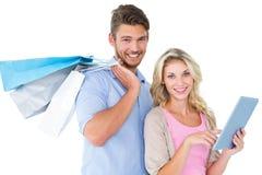 Aantrekkelijke jonge paarholding het winkelen zakken die tabletpc met behulp van Stock Afbeeldingen
