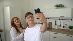 Aantrekkelijke jonge paarman en vrouw die selfies op smartphone thuis in keuken maken Jonge man en vrouwen het nemen stock footage