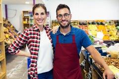 Aantrekkelijke jonge verkopers die camera in de winkel van de gezondheidskruidenierswinkel bekijken Stock Fotografie