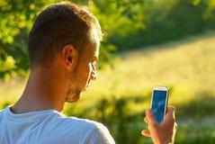 Aantrekkelijke jonge volwassen gebruikssmartphone Stock Fotografie