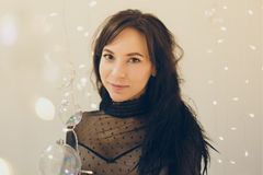 Aantrekkelijke jonge vrouw in cocktailkleding die glimlachend over lichtenachtergrond blijven stock fotografie