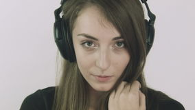 Aantrekkelijke jonge vrouw die aan muziek op hoofdtelefoons luisteren stock videobeelden