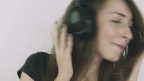 Aantrekkelijke jonge vrouw die aan muziek op hoofdtelefoons luisteren stock video