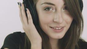 Aantrekkelijke jonge vrouw die aan muziek op hoofdtelefoons luisteren stock footage