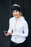Aantrekkelijke jonge vrouw die aan muziek op smartphone luisteren Royalty-vrije Stock Afbeelding