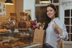 Aantrekkelijke jonge vrouw die bij bakkerijopslag winkelen stock afbeeldingen