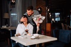 Aantrekkelijke jonge vrouw die bloemen van haar vriend krijgen terwijl het zitten in de koffie royalty-vrije stock foto's