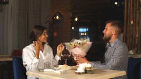 Aantrekkelijke jonge vrouw die bloemen van haar vriend krijgen terwijl het zitten in de koffie stock video