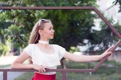 Aantrekkelijke jonge vrouw die buiten stellen Stock Foto's