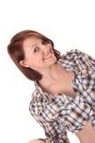 Aantrekkelijke jonge vrouw, die cheekily bij camera glimlacht Stock Foto's