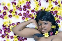 Aantrekkelijke jonge vrouw die in een bed van de Madeliefjes van de Rivier van de Zwaan ligt Royalty-vrije Stock Afbeeldingen