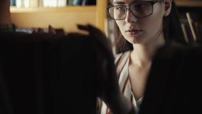 Aantrekkelijke jonge vrouw die een boek van een boekenrek in bibliotheek zoeken stock footage
