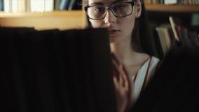 Aantrekkelijke jonge vrouw die een boek van een boekenrek in bibliotheek zoeken stock videobeelden