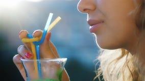 Aantrekkelijke jonge vrouw die een cocktail van de buis drinken Bij zonsondergang, glanst de zon in uw haar, in het zichtbare kad stock video