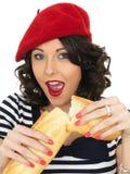 Aantrekkelijke Jonge Vrouw die een Frans Brood van het Stokbrood eten royalty-vrije stock afbeelding