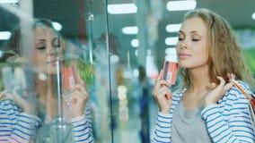Aantrekkelijke jonge vrouw die een glasvitrine bekijken in de opslag De handen die de kaart voor het winkelen houden en stock footage