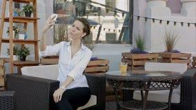 Aantrekkelijke jonge vrouw die een zelfportret op haar celtelefoon nemen, in openlucht stock video