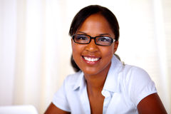 Aantrekkelijke jonge vrouw die en bij u bekijkt glimlacht royalty-vrije stock fotografie