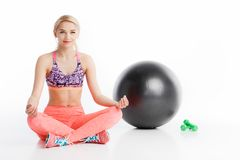 Aantrekkelijke jonge vrouw die en in de positie van de yogalotusbloem inzake de vloer uitoefenen zitten stock fotografie