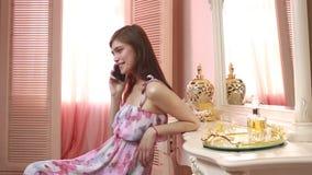 Aantrekkelijke jonge vrouw die en mobiele telefoon thuis houden met behulp van stock videobeelden