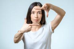Aantrekkelijke jonge vrouw die haar handen gebruiken om een grens tot stand te brengen stock foto's