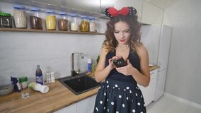 Aantrekkelijke jonge vrouw die haar mobiele celtelefoon in keuken met behulp van stock video