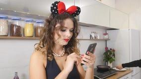 Aantrekkelijke jonge vrouw die haar mobiele celtelefoon in keuken met behulp van stock footage