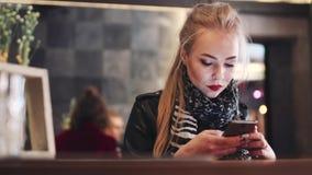 Aantrekkelijke jonge vrouw die haar mobiele telefoon met behulp van terwijl het zitten in café Modieuze vooruitzichten, rode lip stock video