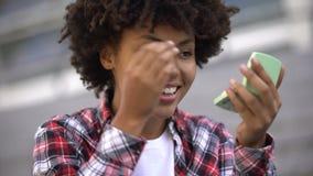Aantrekkelijke jonge vrouw die haar samenstelling aanpassen, die in openlucht in hand spiegel kijken stock footage