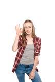 Aantrekkelijke jonge vrouw die o.k. teken tonen en bij camera glimlachen Stock Foto