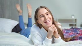 Aantrekkelijke jonge vrouw die op bed liggen die en naakt voeten volledig schot glimlachen spelen stock videobeelden