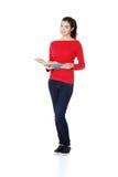 Aantrekkelijke jonge vrouw die open boek, het lezen houden. Stock Afbeeldingen