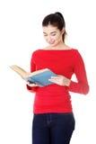 Aantrekkelijke jonge vrouw die open boek, het lezen houden. Stock Foto