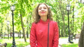 Aantrekkelijke jonge vrouw die in rood jasje ja door hoofd zeggen in openlucht te schudden stock footage