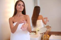 Aantrekkelijke jonge vrouw die room op haar Gezicht toepassen Stock Fotografie