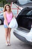 Aantrekkelijke jonge vrouw die in roze kleren zak plaatsen in suv Stock Foto's