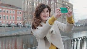 Aantrekkelijke jonge vrouw die selfie in de oude stad naast een rivier nemen stock footage