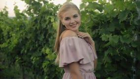 Aantrekkelijke jonge vrouw die terwijl het lopen in wijngaarden stellen stock videobeelden