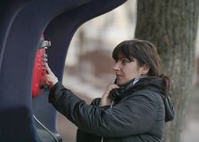 Aantrekkelijke jonge vrouw die van rode straatpayphone roepen royalty-vrije stock afbeelding
