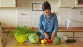 Aantrekkelijke jonge vrouw die zich bij keukenlijst en scherpe groenten bevinden Gezonde levensstijl, organisch voedsel, veganist stock videobeelden
