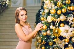 Aantrekkelijke jonge vrouw in een roze elegante avondjurk die in een elegante zaal blijven en omhoog een Kerstmisboom met gele ba royalty-vrije stock afbeeldingen