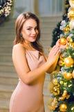 Aantrekkelijke jonge vrouw in een roze elegante avondjurk die in een elegante zaal dichtbij Kerstmisboom blijven met gele bal in  royalty-vrije stock foto's