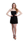 Aantrekkelijke jonge vrouw in een zwarte kleding die en c glimlachen bekijken Stock Afbeelding