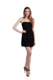 Aantrekkelijke jonge vrouw in een zwarte kleding die en c glimlachen bekijken Stock Foto's