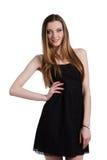 Aantrekkelijke jonge vrouw in een zwarte kleding die en c glimlachen bekijken Royalty-vrije Stock Afbeeldingen