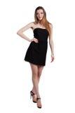 Aantrekkelijke jonge vrouw in een zwarte kleding die en c glimlachen bekijken Royalty-vrije Stock Foto