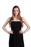 Aantrekkelijke jonge vrouw in een zwarte kleding die en c glimlachen bekijken Royalty-vrije Stock Afbeelding